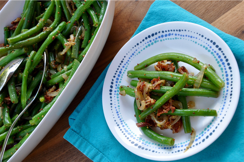 Bacon & Mustard Spiked Green Beans on a serving bowl and plate